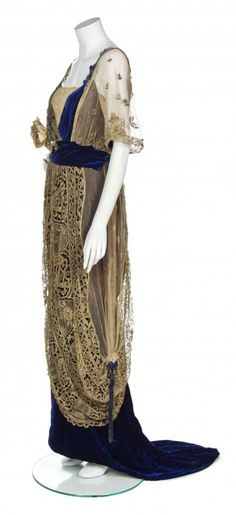 A Maison Worth Cobalt Blue Silk Velvet and Gold Lace Gown,circa 1910,cobalt blue underdress with a peach velvet inset to the V-neckline, gold lace and net overlay, with a velvet cummerbund and silk flower embellishment at the bust, lightly boned, with a small weighted hem train. Labeled to waist: C. Worth. Sideway