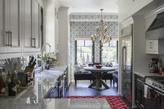 French Contemporary Eclectic Kitchen: White upper cabinets, black lower cabinets, and a bright-red rug in an L.A. kitchen.