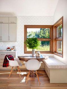 cuisine blanche et bois, table ronde en bois et banquette d'angle