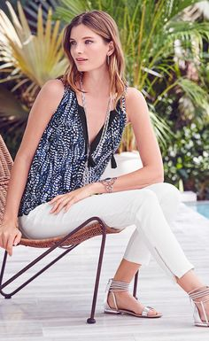 Topped with a notch neck, tucked pleats and tasseled-ties, this easy tank in feather print creates a blouson silhouette from a banded smock hem.   White House Black Market