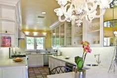 Hollywood Spanish Revival kitchen remodeled with marble counters, seeded glass front upper cabinets, small eat in counter, round prep sink and Murano chandelier (especially love this!).