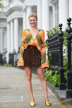 Pandora Sykes in an orange and green long sleeve patterned blouse, high-waisted chocolate brown skirt, and gold heels.