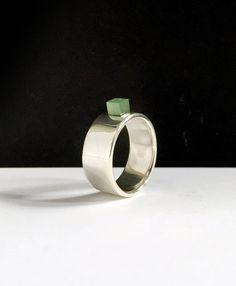 Deze stevige en stoere zilveren ring heeft een klein vierkant groen steentje. De ring heeft een hoogglans gepolijste afwerking. De ringmaat van dit exemplaar is 18,2 mm en kan slechts nog een keer bijbesteld worden. De ring draagt uiterst comfortabel en zacht.