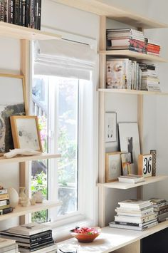 shelves around window: a painted feature wall behind in a room of all white, popping behind shelves full of books! Oh yes!
