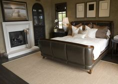 Elegant, dark leather-bound bed frame is the centerpiece of this bedroom featuring a white fireplace with large mantle artwork and a built-in dark wall cabinet matching the furniture.