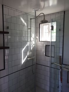 Great way to keep a bathroom simple and elegant all at the same time. Black grout used with white porcelain tile, frameless glass doors and black accent lines to finish it off.