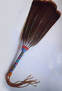 Flat Fans are formed from a group of carefully matched feathers fixed into a handle which is then beaded in eye-catching peyote stitch beadwork. Plied deerskin tassels hang from the base of the fan's handle. Theses fans are often used for smudging and blessing, as well as for healing work. http://www.nicholaswood.net/Pages/Feathers.htm