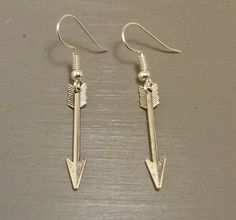 Complete your look with this silver arrow earrings. These earrings are made with silver metal alloy arrow charms and french ear wire. The total length of these dangle earrings are 1.75 inches.