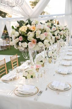 Long, rectangular tables were swathed in white linens and topped with towering centerpieces composed of roses, hydrangeas, garden roses, and crystal garlands. #receptiondecor Photography: Michael Segal Photography. Read More: http://www.insideweddings.com/weddings/poolside-ceremony-amazing-open-air-tented-reception-in-california/641/