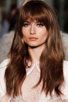 Lange kastanienbraune Haare mit Pony, blaue Augen und pfirsichfarbene Lippen, weißes Kleid mit Spitzenmotiven