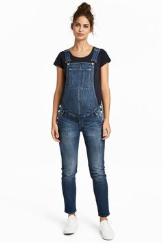 Denim blue. Bib overalls in washed stretch denim with distressed details and adjustable suspenders. Bib pocket, side and back pockets, buttons at sides, and