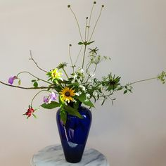 A dance of seasonal flowers, with seed heads, sweet peas, rudbeckia, scabiosa, ammi majus, twigs and other foraged elements from the farm.