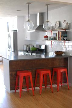 Renovation Diary: Sandra & Justin's Kitchen (from AT) -- like red stools, globe lights, color scheme (wt, gray, brown, red), wood on back of peninsula