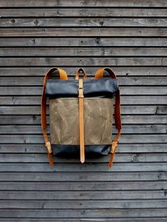 Waxed canvas backpack with leather roll to close top and vegetable tanned leather shoulderstrap and back reinforcement