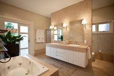"""No banheiro da suíte, as paredes são revestidas por cacos de Limestone """"em cubinhos"""" e combinam com a pia e a banheira. O rodapé, também em Limestone, foi desenhado na altura do vaso sanitário e a pintura das paredes é direta sobre o emboço cru. O projeto arquitetônico é de Maurício Karam."""