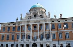 Photo made an important and historic building in Trieste in Friuli Venezia Giulia (Italy). In the picture we see the central part of the front three-story, full of six columns and many statues placed on top as the perimeter of a dome with blue sky above, an important palace.