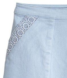 Ljusblå. En kort kjol i stretchig bomullstwill. Kjolen har två sidfickor med spets längs kanten. Dold dragkedja i sidan.