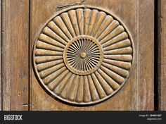 Simple circle shape representing the sun, carved on a wooden surface.