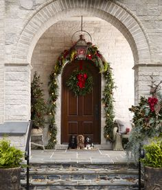 Beautiful outdoor Christmas decorations on stone house with arched door and three dogs at door