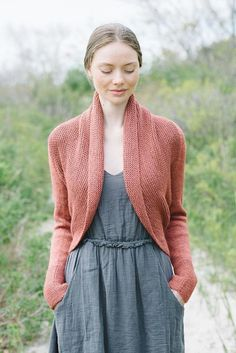 This shrug is worked side to side from cuff to cuff. Sleeves are worked in the round, the back is worked flat, then the band is picked up around selvedge edges of back and worked in the round, making a pretty shawl collar.The sample shown was knit in The Fibre Co. Canopy Worsted, shade Acai. Substitute yarns are recommended below.