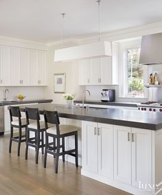 Contemporary White Kitchen With Quartz Countertops, Mid Tone Floor And White  Cabinets.