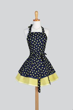 Womens Aprons: Creative Chics retro ruffled full womans apron is sophisticated yet flirty with a vintage style full skirt. A cute kitchen cooking apron makes a great personalized gift by adding a monogram or embroidery (sold separately), especially for moms and brides. This apron is made in fun navy blue and citron bandanna print. This also makes a unique house warming or hostess gift.  Care Instructions: Machine Washable  Sizing: One size fits most Length from bodice to hemline: 28 Waist…