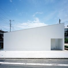 the single-storey house by satoshi kurosaki and apollo architects is located in a residential neighborhood in hodogaya ward , yokohama. love the glow of the all white outside and the definition of the space by the black window frames. the kitchen, set up like a bar, offers equally communication and retreat with the bare minimum of elements.