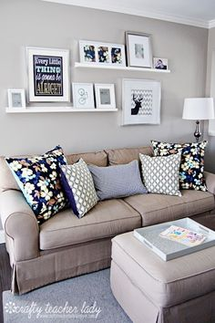 Above the couch simple plank floating shelves (could also do on mantle). Uses large frames mounted on the wall and small picture frames propped up on the shelves. Note all frames and shelves are white
