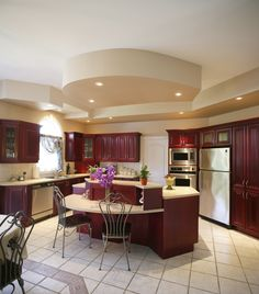Red wood features heavily in this kitchen, contrasting with light beige tile flooring and countertops. Elaborate, multi-tiered island has built-in bread box and ample dining space.