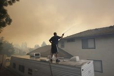 Week of Apr 26-May 2, 2014  A homeowner sprayed water on his house as a wildfire closed in on him in Rancho Cucamonga, California, on Wednesday. The brush fire forced the evacuation of about 1,000 residents north of the town, officials said. (David McNew/Reuters)