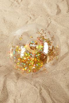 A clear beach ball by Pool Candy™ featuring iridescent gold confetti enclosed in the ball.