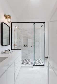 Bathroom Decorating Ideas. Walk in shower. Modern bathroom features a black framed shower enclosure filled with marble tiles fitted with a tiled shower niche as well as a polished nickel vintage gooseneck shower head over a black and white geometric tiled floor.