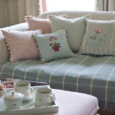 Susie Watson Designs - Susie Watson Designs Fabric Collection - Blue throw with white stripes forming square patterns. Cushions in pastel shades with strips and floral patterns. Candy striped footstool.