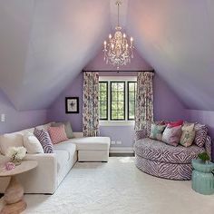 2 Design Group - girl's rooms - Benjamin Moore - Whisper Quiet - lilac colored walls, purple walls, purple wall color, dormer ceiling, dormer ceiling girls room, purple walls and ceiling, painted ceiling, crystal chandelier, ivory sectional sofa, ivory sectional with chaise, purple zebra print pillow, pink geometric pillow, turned wood pedestal table, floral curtains, steel framed window, purple accent chair, round lounge chair, zebra print lounge chair, girls hangout room, union jack…