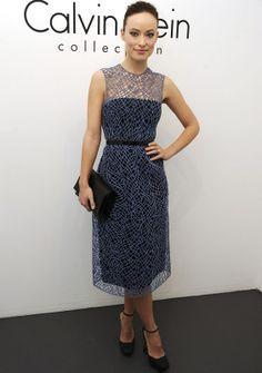 Olivia Wilde con un vestido de Calvin Klein colección primavera de 2013 strapless en negro con un segundo cuerpo de líneas geométricas en azul grisáceo entallado a la cintura con un cinturón de piel XS también negro.