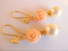 Oorbellen Sweet Rose  Witte grote swarovski parels met een perzik koraal roos en roos oorhaken. Geheel goud op zilver.