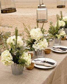 Hortensias, westringias y pittosporum blancos sobre baldes de zinc y manteles de lino de arpillera.