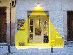 the facade of a vegan restaurant has been illuminated for 4 days and nights by more than 250 meters of yellow tape, pineapples, painted pieces of art, lawn furniture and a lamp.