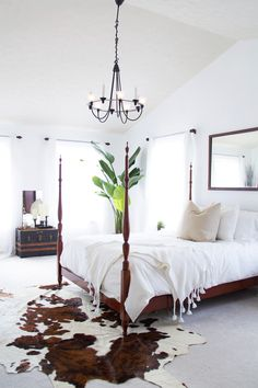 four poster bed with metal chandelier, and cowhide rug. simple and rustic bedroom design
