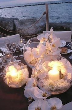 White orchids and candles in bubble vases for a beautiful beach inspired centerpiece