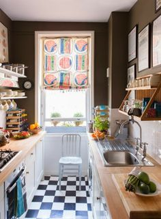 Galley kitchen-butcher block counters, black/white checked flooring, open shelving, sink with integrated drainboard. Finishes are inspired-colorful window shade and brown walls.