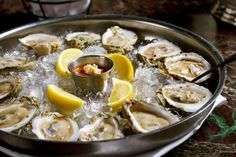Fresh raw oysters with lemons on ice in metal tray - nmaxfield/E+/Getty Images