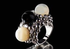 Der Ring in Rhodium ist von Perlen und zarten Farben inspiriert. In den vielen kleinen weissen Kristallen finden sich drei grosse feminine Perlen in Weiss und Grau und sind das Highlight des handgemachten Ringes.  925er Sterling Silber Rhodium überzogen Weiss Perle, Grau Perle Zirkonia weiss