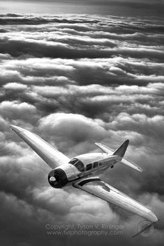 B&W photograph of a Spartan Executive above the clouds.