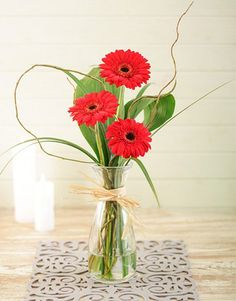 Red mini gerberas fixed in a glass milk bottle completed with greenery