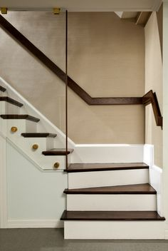 Flat contrasting handrail//glass extending to ceiling//brass detail.
