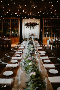 Rustic wedding reception with greenery table runner and cafe lights | Image by The Hursts & Co.