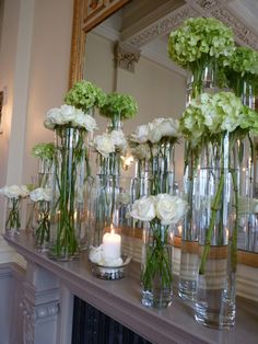 Tall vases of flowers and a candle for the mantelpiece