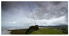 'Wind Wand'  (red fibreglass tube) by Len Lye at Gibbs Farm, Kaipara Harbour, New Zealand.
