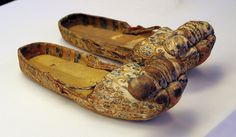 Tang Dynasty. Brocade shoes with rolled toe-caps. The most unusual feature of these shoes is the upturned cloud shapes made in the same color brocade on the tips of the shoes. The 'clouds' are stuffed with brown grass. These shoes could have been worn by men or women. Excavated from Tomb No. 381, Astana, Turfan. Xinjang Uygur Autonomous Region.